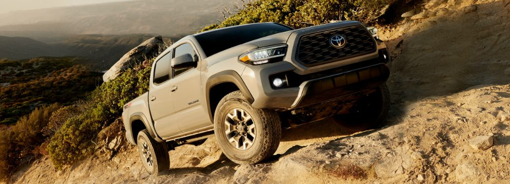 Grey 2020 Toyota Tacoma driving up a rocky hill
