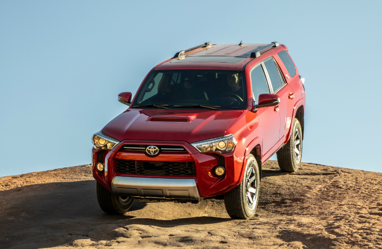 Red 2020 Toyota 4Runner driving down a rocky hill