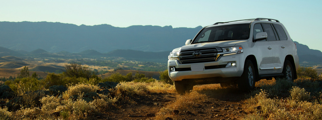 White 2020 Toyota Land Cruiser driving on a rocky path