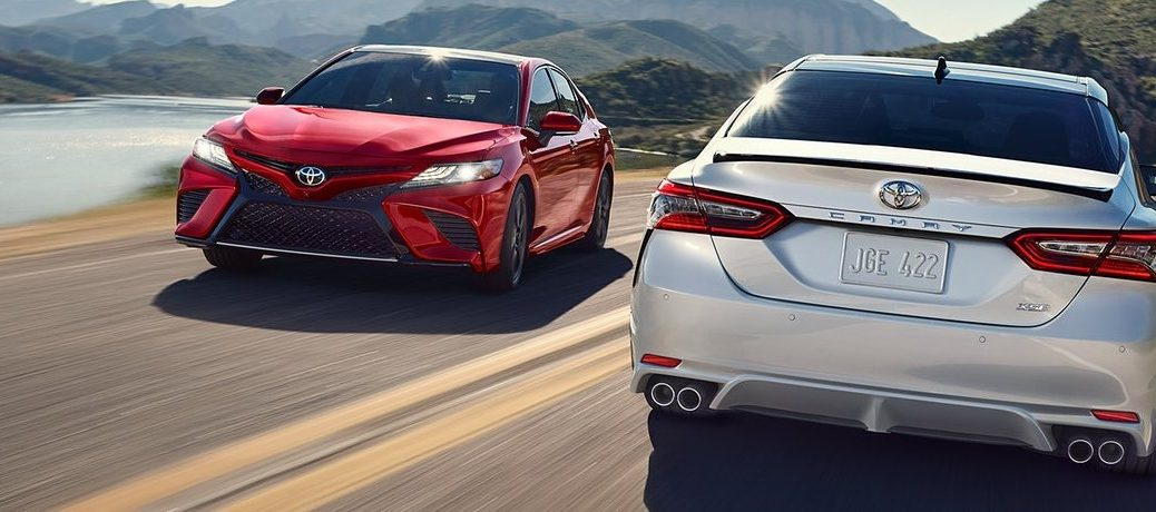 Front view of red 2020 Toyota Camry and rear view of silver 2020 Toyota Camry