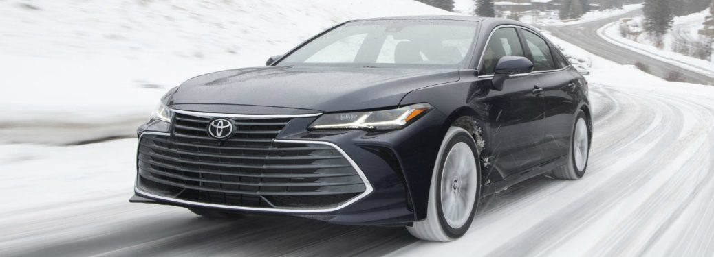 Driver's side front angle view of dark blue 2020 Toyota Avalon driving on a snowy road
