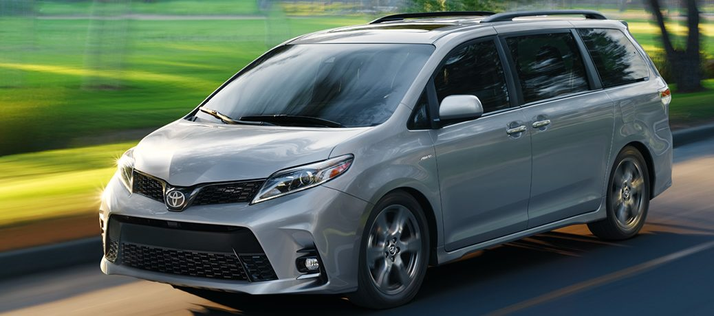 Silver 2020 Toyota Sienna driving by a field
