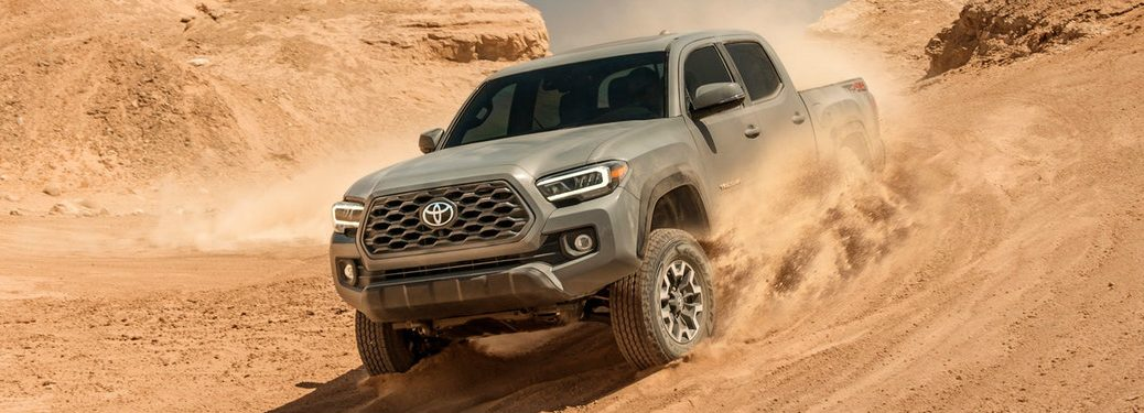 Grey 2020 Toyota Tacoma driving down a sand dune