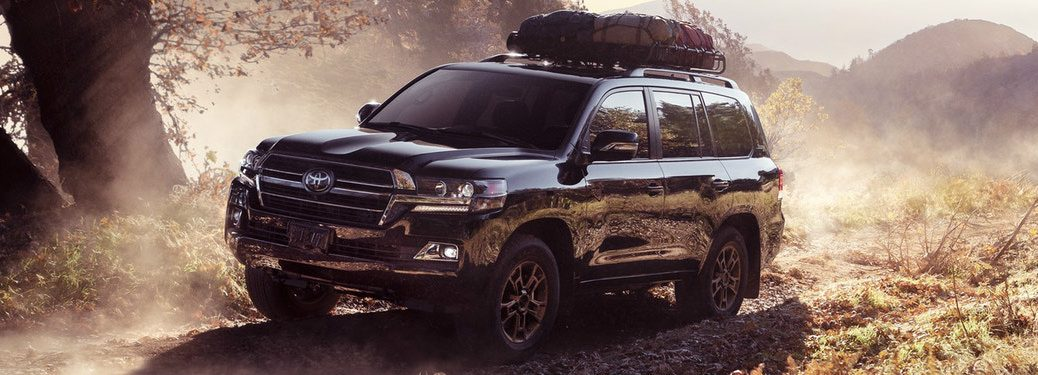 Black 2020 Toyota Land Cruiser driving on a dusty trail