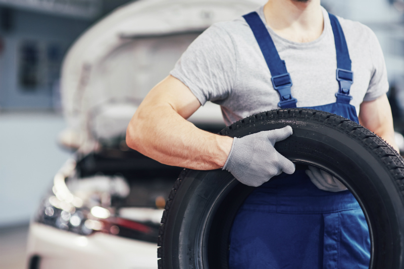 A mechanic holding a tire in front of a white car
