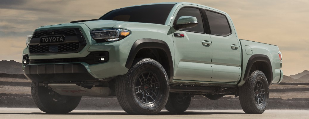 Driver's side front angle view of light green 2021 Toyota Tacoma