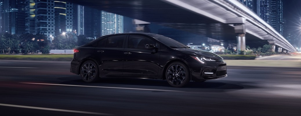 Black 2021 Toyota Corolla driving on a street at night
