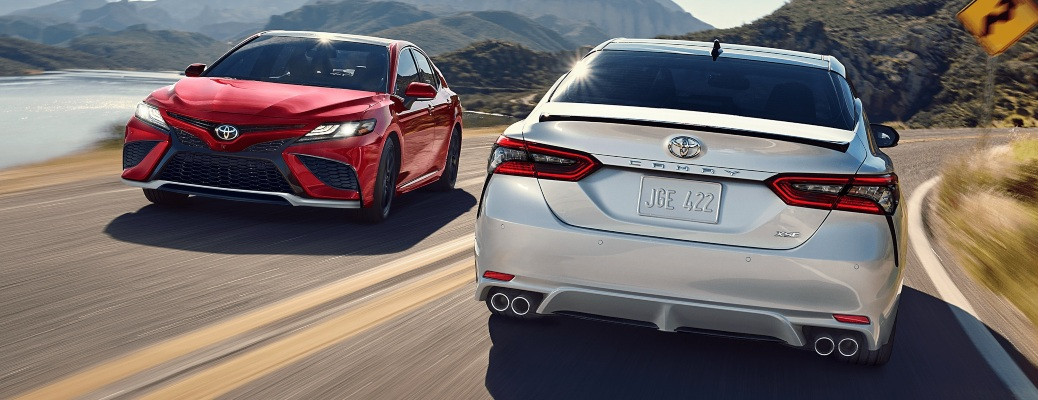 2021 Toyota Camry sedans passing on a highway red and white