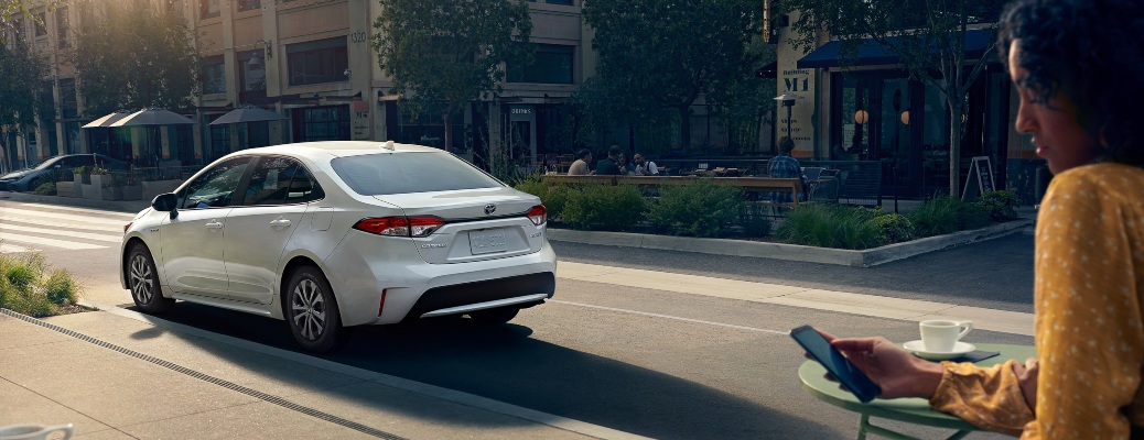 2021 Toyota Corolla white back view with woman and phone