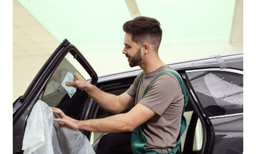 man cleaning a tinted window on a car with a few rags