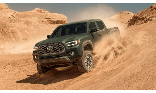 2021 Toyota Tacoma green driving through dusty sand in desert