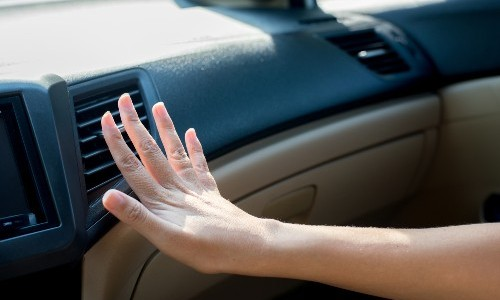 hand in front of air vent in car sunlight and shadow