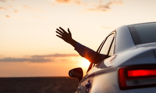 person sticking arm out window near sunset