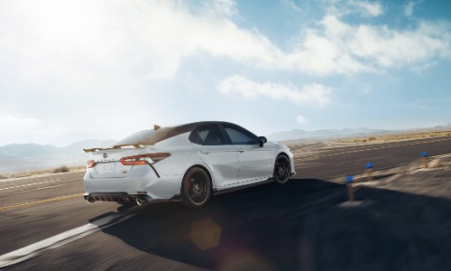 2021 Toyota Camry white with spoiler driving around curved road