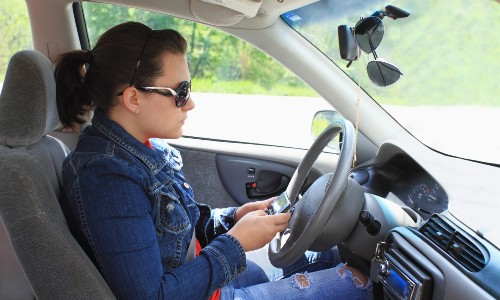 young woman texting and driving