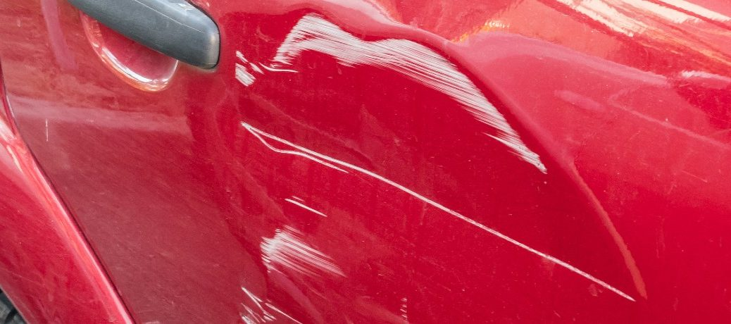 white paint scuffs on red car close up