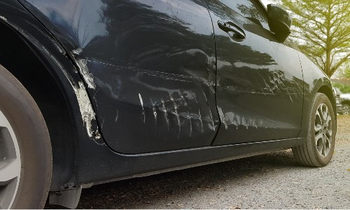 black car with damaged passenger side paint and doors