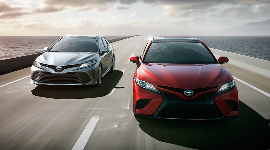 White and red 2018 Toyota Camry driving on road