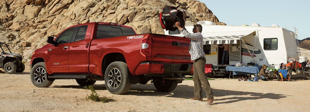 Man loading a backpack into the bed of the 2018 Toyota Tundra