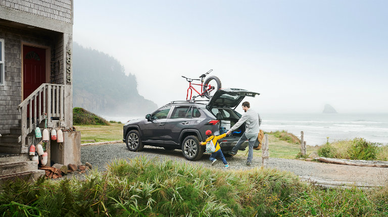 A man and boy loading up the 2019 Toyota RAV4 by a house