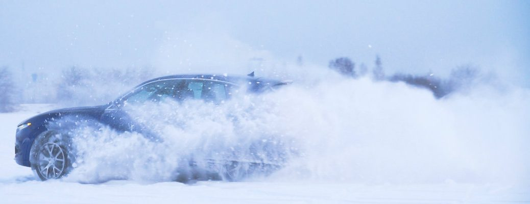 A sedan driving through the snow