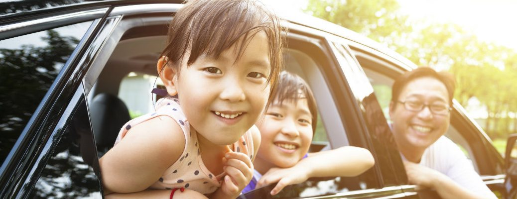 A girl and her family smiling out the windows of a car