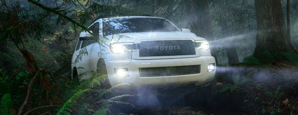2020 Toyota Sequoia TRD Pro driving through the forest with its lights on at night