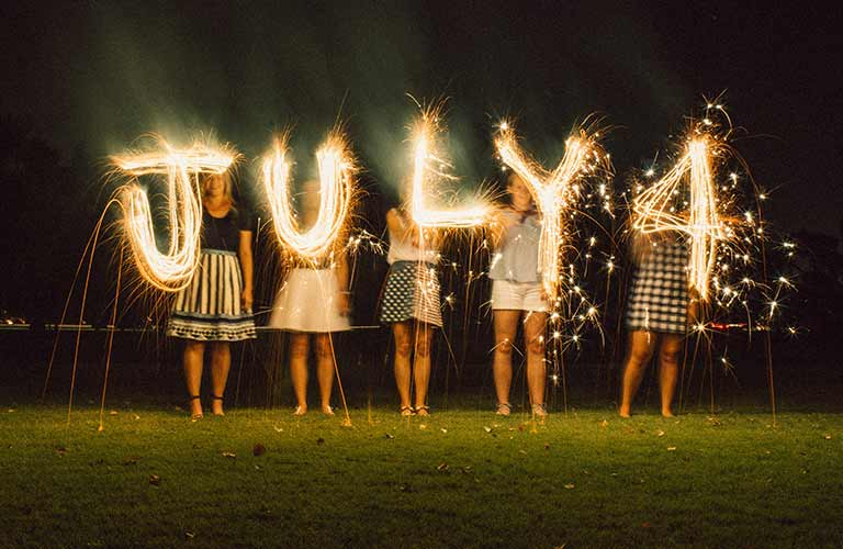 """Four people holding up lights that together spell """"July 4"""" against a night sky"""