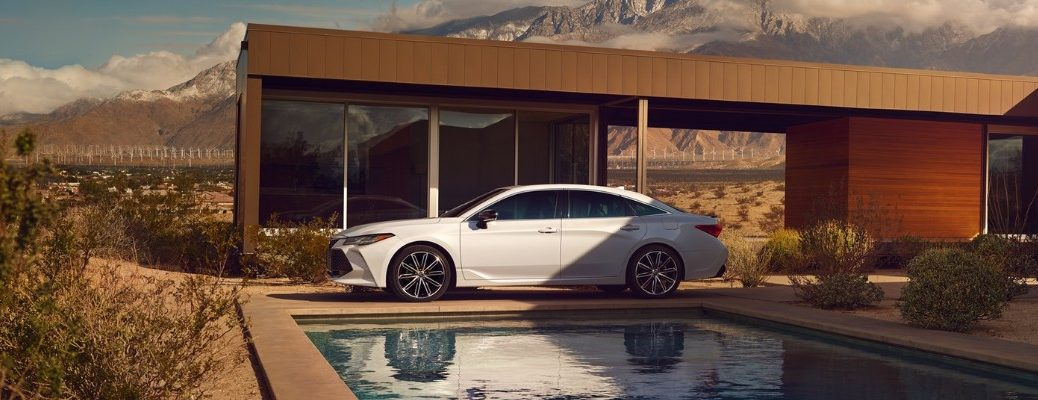 2020 Toyota Avalon in front of a swimming pool near a luxury home near the mountains