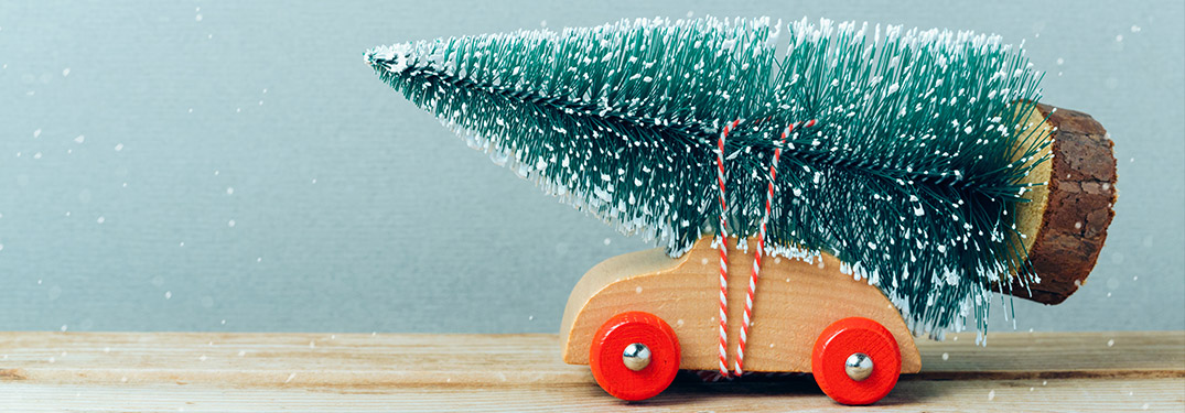 A toy car with a toy Christmas tree tied to the top of it