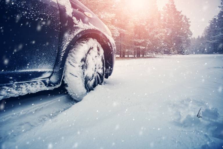 A car tire stock in the snow