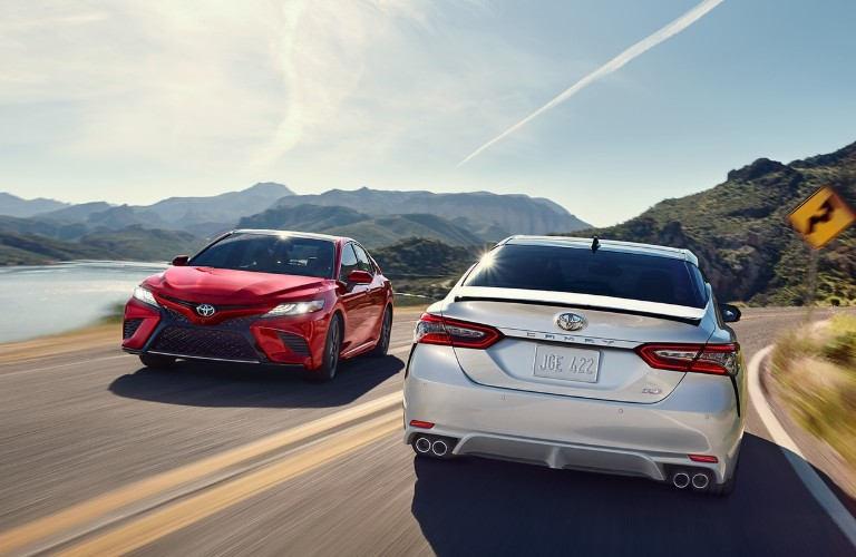 Two, 2020 Toyota Camry sedans driving on the highway past each other