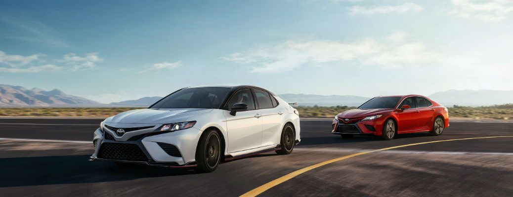 White and red 2020 Toyota Camry models driving