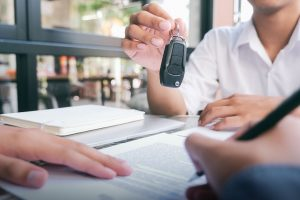 Salesman holding car keys while person signs paperwork