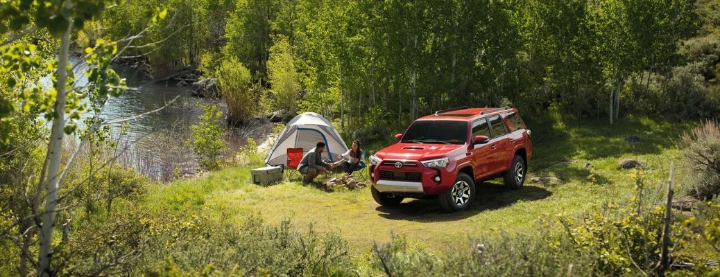 Couple tent camping next to a 2020 Toyota 4Runner