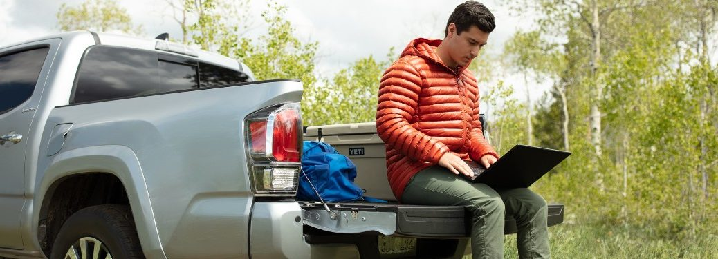 A man sitting on the tailgate of a 2021 Toyota Tacoma