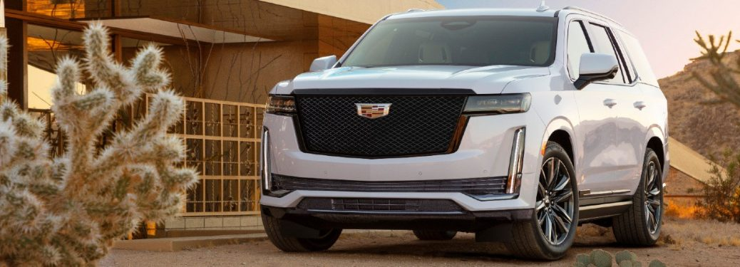 2021 Cadillac Escalade exterior front shot with white paint color and new mesh grille parked in the desert near dry plants and a beige building