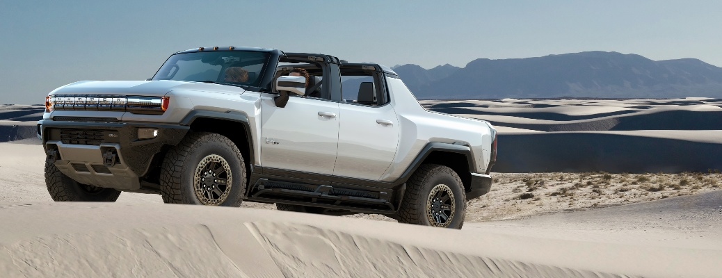 2022 GMC Hummer EV going up a sandy hill