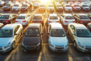 Hundreds of vehicles in parking lot with sun shining