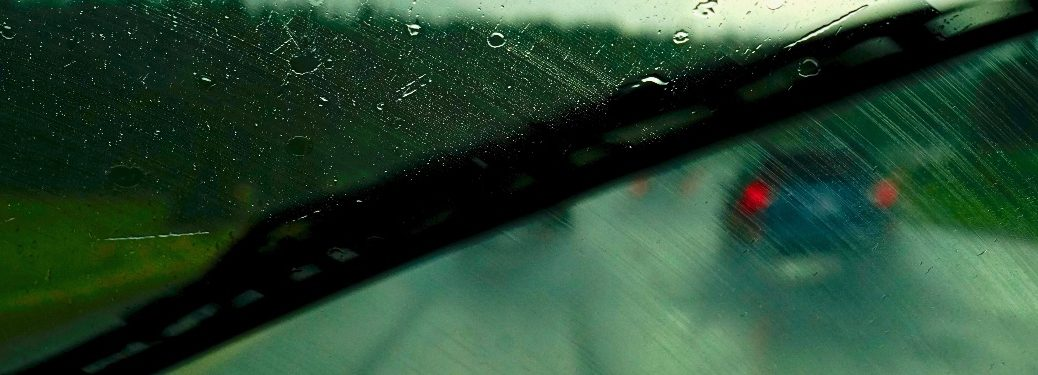 windshield wiper close up with greenish tint and raindrops