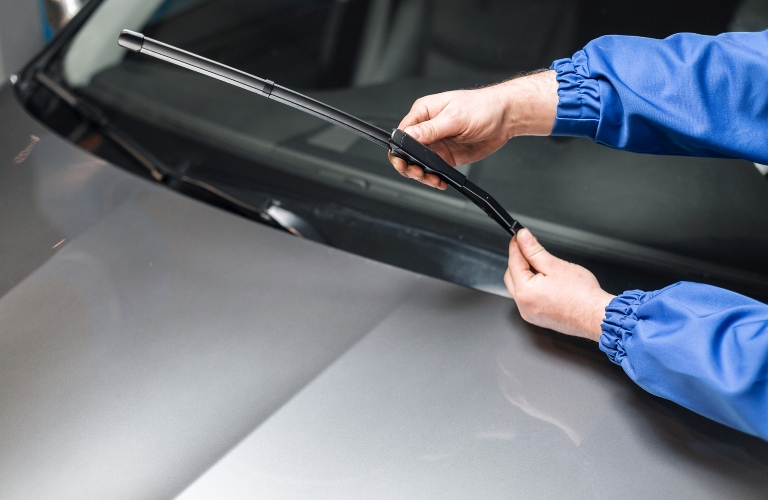 person replacing windshield wiper blade