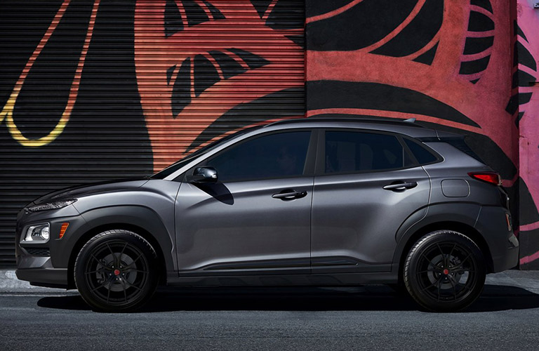 2021 Hyundai Kona exterior driver side profile in front of spray painted garage art