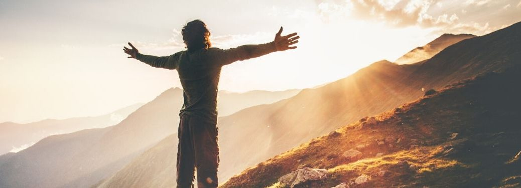 person with arms spread in front of mountains with sunlight