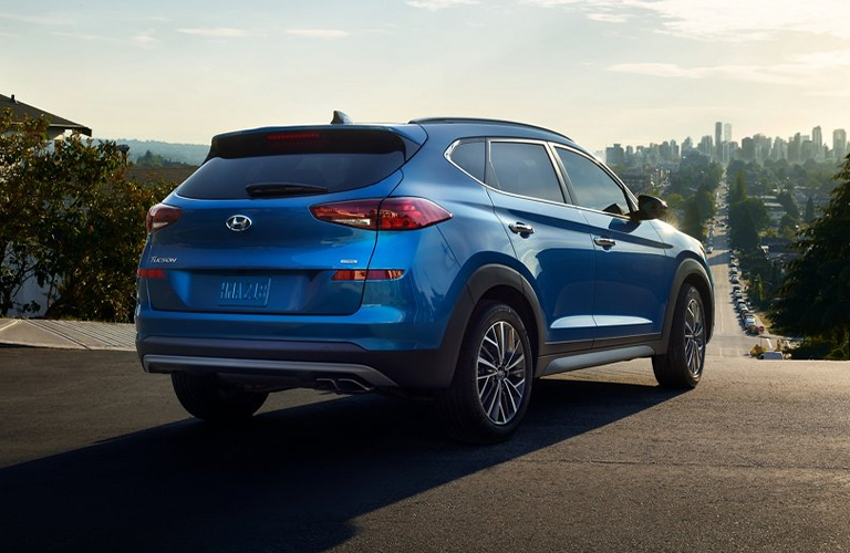 2021 Hyundai Tucson exterior rear fascia passenger side on hill with trees and city in distance