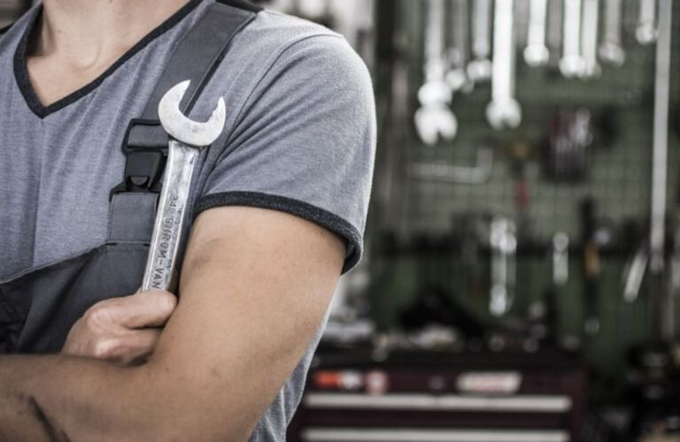 Mechanic in gray shirt holding wrench with blurred background