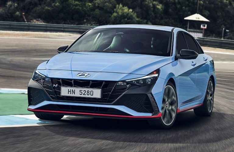 Front fascia of a blue 2022 Hyundai Elantra N while cornering on a race track