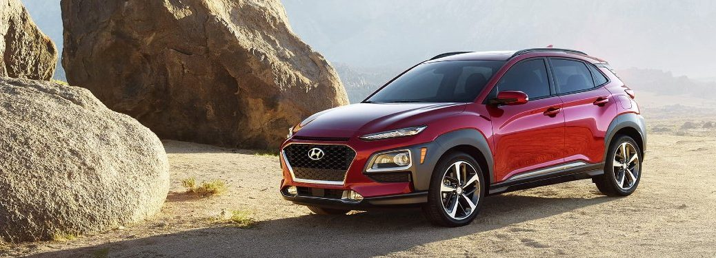 Front driver angle of a red 2020 Hyundai Kona parked near boulders