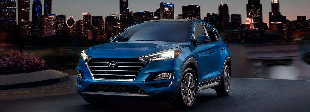 Front driver angle of a blue 2020 Hyundai Tucson with a city in the background