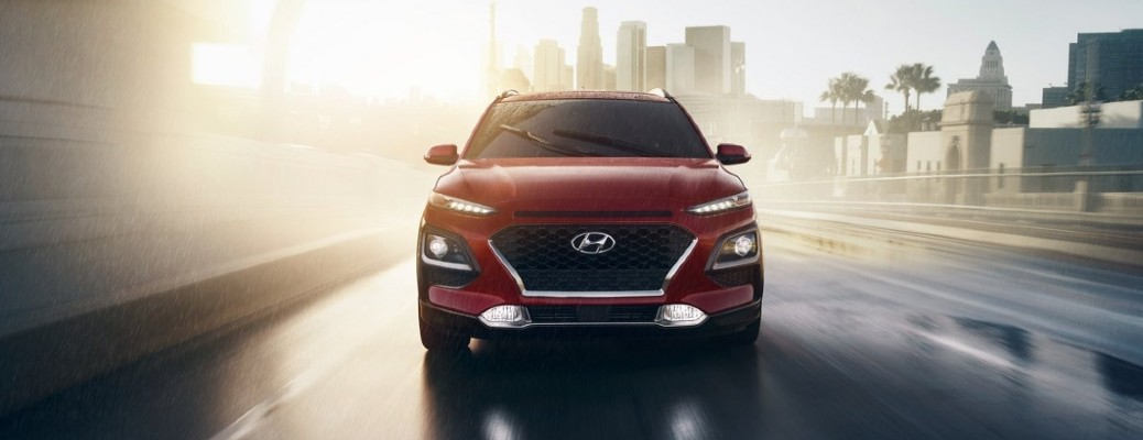 A front view of a red 2021 Hyundai Kona with the sun beating behind it.