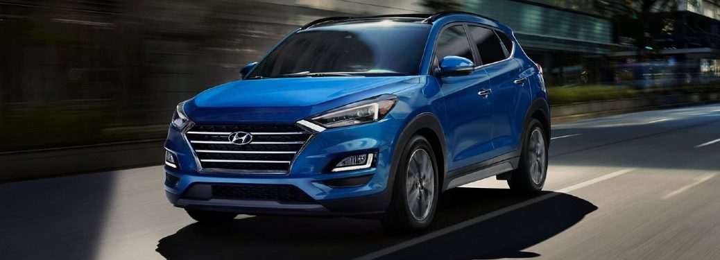 Front driver angle of a blue 2021 Hyundai Tucson driving in a city